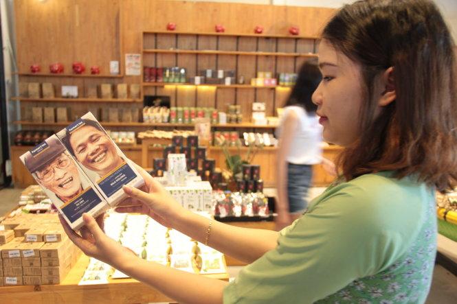 Du khách thích thú với mặt hàng cà phê với hình ảnh nhận diện thương hiệu dung dị.-Ảnh: Trường Trung