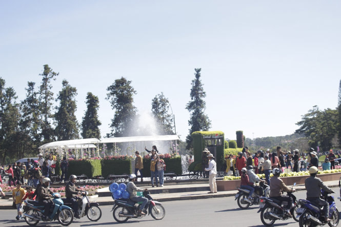 Du khách chụp ảnh bên đoàn tàu kết hoa giữa vòng xoay cầu Ông Đạo, khu vực trước chợ đêm Đà Lạt - Ảnh: C.Thành